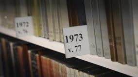 Scaffale per libri con gli archivi Vecchi libri storici multicolori in biblioteca video d archivio