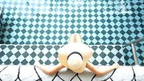 Scaffale vago nel deposito di libro per fondo Donna in cappello di paglia d'uso del bikini nella piscina archivi video
