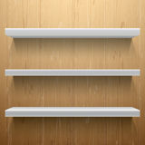 Scaffali bianchi su fondo di legno Fotografia Stock Libera da Diritti