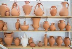 Scaffali con differenti barattoli e vasi marroni dell'argilla Fotografia Stock Libera da Diritti