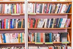 Scaffali con i libri nella biblioteca Fondo vago degli scaffali per libri Istruzione e scienza Deposito di libro, istruzione e immagine stock
