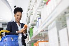 Scaffali di Holding Medicine By della donna di affari in farmacia Immagine Stock