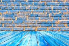 Scaffali di legno della plancia e fondo blu del muro di mattoni Per PR fotografie stock libere da diritti