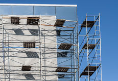 Scaffold against a white wall. Of the new building Royalty Free Stock Photo
