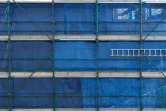Scaffold and blue hoardings with ladder on construction site Royalty Free Stock Image