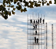 The Scaffold Builders. A group of construction workers in silhouette build tall scaffolding against a background of blue sky with puffy clouds Stock Photos