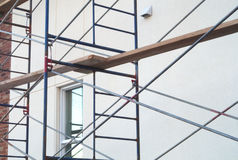 Scaffold construction site white concrete wall renovation. Construction renovation wall scaffolding structure Royalty Free Stock Photography