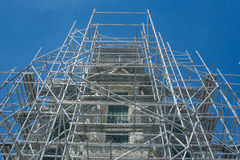 Scaffold. Surrounds this old pagoda in against a deep blue sky Stock Photo