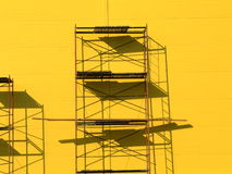 Scaffolding. Constructions scaffolding on the yellow wall background Stock Images