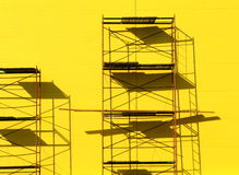 Scaffolding. Constructions scaffolding on the yellow wall background Stock Photos