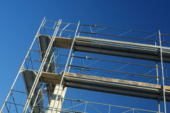 Scaffolding. On a construction site, against a clear blue sky Stock Photography