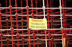 Scaffolding. A red and grey big scaffolding with yellow warning sign DANGER CONSTRUCTION WORK OVERHEAD in the middle Royalty Free Stock Photos