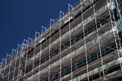 Scaffolding. New building covered in a scaffold at a construction site with blue sky in the background Royalty Free Stock Photo