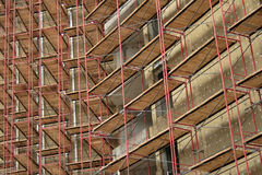 Scaffolding on apartment building. Repeating pattern of scaffolding on apartment building. Horizontal format version stock image