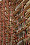 Scaffolding on apartment building. Repeating pattern of scaffolding on apartment building. Vertical format version stock photo