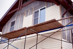 Scaffolding around house with beige siding covering walls. Construction site royalty free stock image