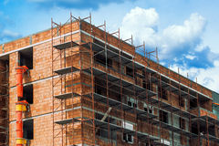 Scaffolding around new unrendered building at construction site Royalty Free Stock Photo