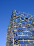 Scaffolding and Blue Safety Cladding on Construction. A multi level building under construction with scaffolding and blue nylon safety cladding, and a clear blue Stock Images