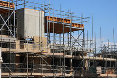 Scaffolding and building work. Scaffolding around a construction site as a new building emerges. Homes for the future Royalty Free Stock Photo