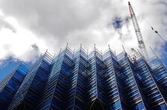 Scaffolding on building. Worker and a crane in the background. Royalty Free Stock Image