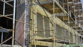 Scaffolding on a construction site in daylight. Builder`s equipment by unfinished building stock video footage
