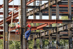 Scaffolding construction workers. Industrial workers elevated on scaffolds are working hard on a construction site for building a new office building Royalty Free Stock Images