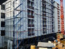 Scaffolding in front of building under construction. NONTHABURI, THAILAND - APRIL 18, 2018: A crane stands in front of a building under construction on April 18 royalty free stock image