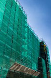 Scaffolding with green network. Modern building is under construction, metal scaffolding with green network cover against blue sky stock photos