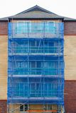 Scaffolding on a House with Safety Net. Scaffolding on a new modern residential house with blue safety net stock photos