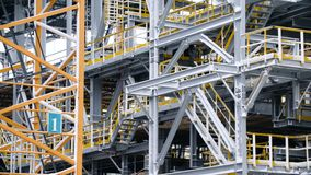 Scaffolding installation at a tank with process structures of refinery petrochemical plants in the background. Large Royalty Free Stock Photos