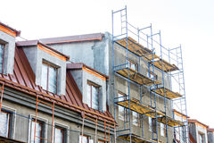Scaffolding near house under construction. facade renovation. Royalty Free Stock Image