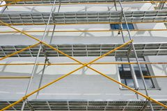 Scaffolding near a new house, building exterior, construction and repair industry, white wall and window, yellow pipe stock images