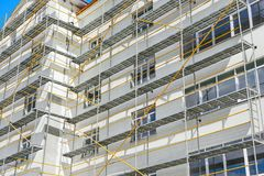 Scaffolding near a new house, building exterior, construction and repair industry, white wall and window, yellow pipe royalty free stock photo