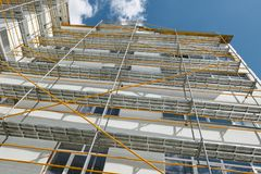 Scaffolding near a new house, building exterior, construction and repair industry, white wall and window, yellow pipe stock image