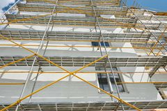 Scaffolding near a new house, building exterior, construction and repair industry, white wall and window, yellow pipe royalty free stock image