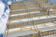 Scaffolding near a new house, building exterior, construction and repair industry, white wall and window, yellow pipe royalty free stock photography