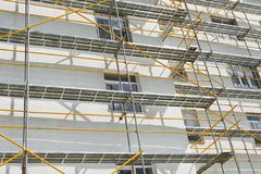 Scaffolding near a new house, building exterior, construction and repair industry, white wall and window, yellow pipe stock photo