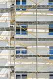Scaffolding near a new house under construction, white wall and window, yellow pipe royalty free stock photos