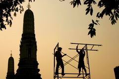 Scaffolding, Wat Arun. Two silhouetted workers building a scaffolding. Wat Arun, aka Temple of Dawn, is a buddhist temple in the Bangkok Yai district, on the royalty free stock photos