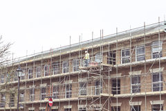 Scaffolding. A worker at a building site with scaffolding in the UK royalty free stock image