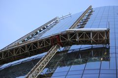 Scaffoldings on under construction tower glass wall. Royalty Free Stock Photography