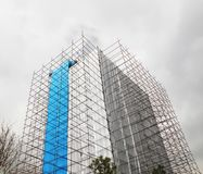 Scaffolds. Scaffolding unfinished building covered with plastic sheets Royalty Free Stock Image