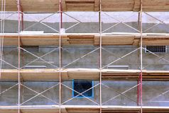 Scaffolds on building. Metal rail and wooden toe-board scaffolds on a building, close-up Royalty Free Stock Photo
