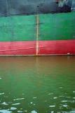 Scafo di navi variopinto con la striatura ed acqua della ruggine Fotografia Stock