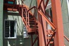 Scala d'acciaio rossa dalla parete verde fotografia stock