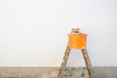 Scala del pittore e secchio davanti ad una parete esterna vuota Fotografia Stock Libera da Diritti