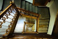 Scala della scala La vecchia annata ha quadrato le scala a spirale delle scale di multi-volo con i corrimani marroni del metallo  immagine stock