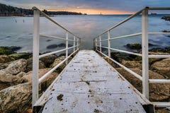 Scala di legno che conduce al mare, faro in priorità alta Fotografia Stock Libera da Diritti