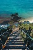Scala di legno che conduce alla costa di mare, nel concetto di vacanza della destinazione di viaggio di alba di mattina fotografie stock