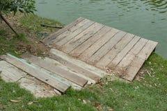 Scala di legno giù allo stagno fotografia stock